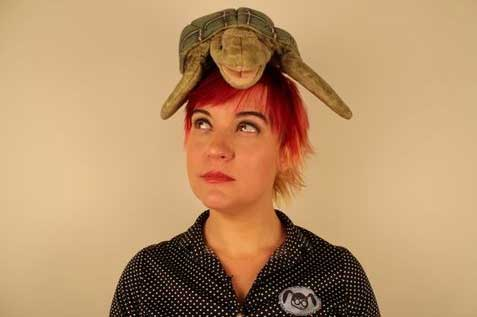 Reviewer Erin Rodgers, a red-headed woman with plush sea-turtle on her head