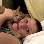 Audra Williams snuggling an orange kitten.