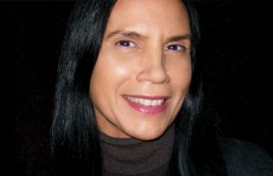 Head shot of composer and singer Barbara Assiginaak. She is wearing a brown turtleneck and is looking at the camera and smiling.