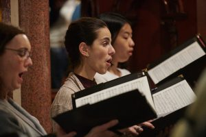 Three female choristers are singing during a rehearsal. We see them from the side. They are holding black music folders.