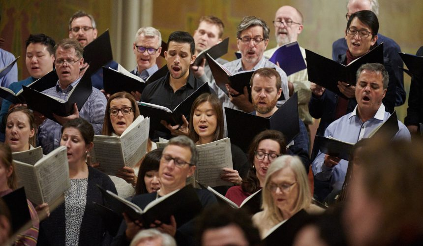 A group of choristers are singing during rehearsal. They stand in rows with women in front of the men. They are all holding music.