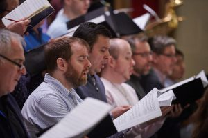 A row of male choristers are singing during rehearsal. They are all holding music.