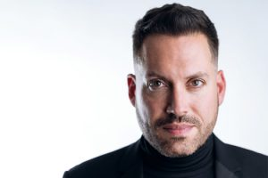 Head and shoulders photo of Artistic Director Jean-Sebastien Vallee. He is wearing a black turtle neck and jacket and is looking directly at the camera.