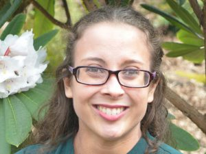 Headshot of Rena who has curly cark hair and is wearing glasses. She is standing in front of a rhododendron