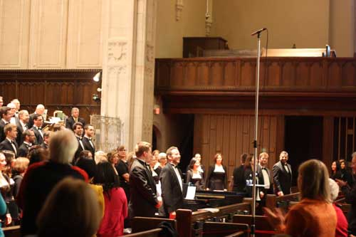 Symposium conductors and Jim Bourne standing to take bows in front of the TMC, as the audience applauds at Yorkminster Park Baptist Church