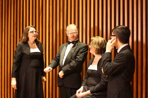Two men choristers and two women choristers wearing safety goggles and concert attire in front of a wood panelled wall.